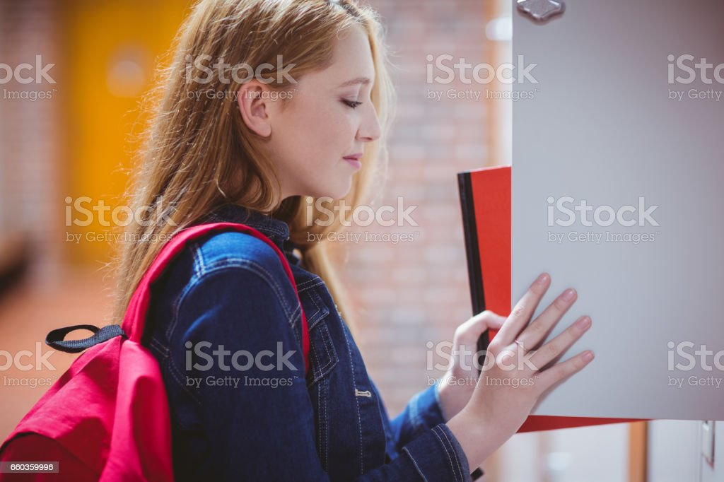 Pretty student with backpack putting notebook in the locker stock photo