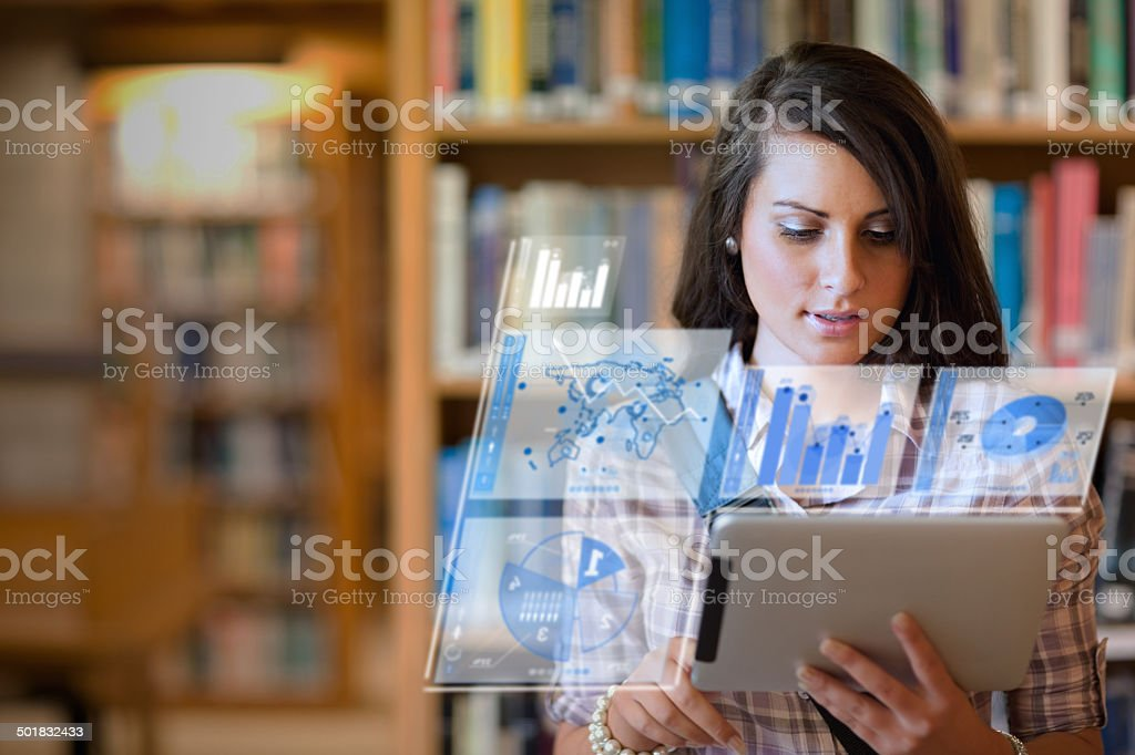 Pretty student working on her futuristic tablet stock photo