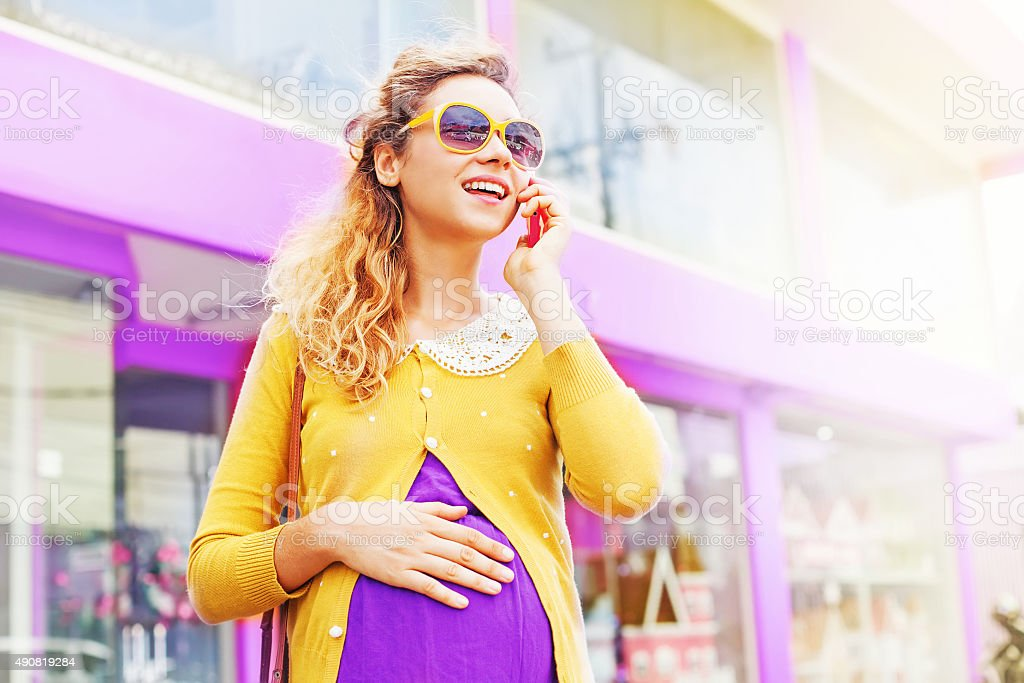 Pretty stylish pregnant woman on a street with mobile phone stock photo