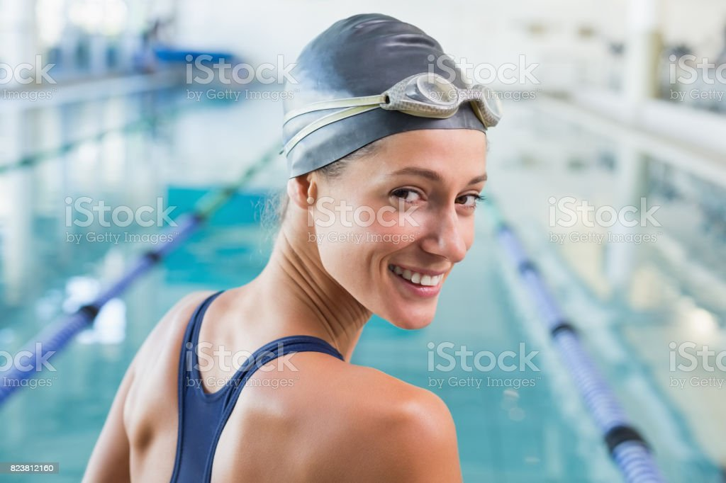 Pretty swimmer by the pool smiling at camera stock photo