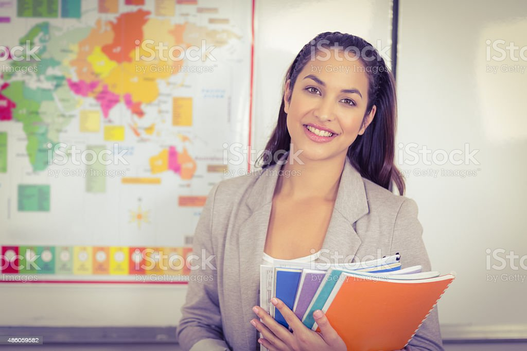 Pretty teacher holding notepads in a classroom stock photo