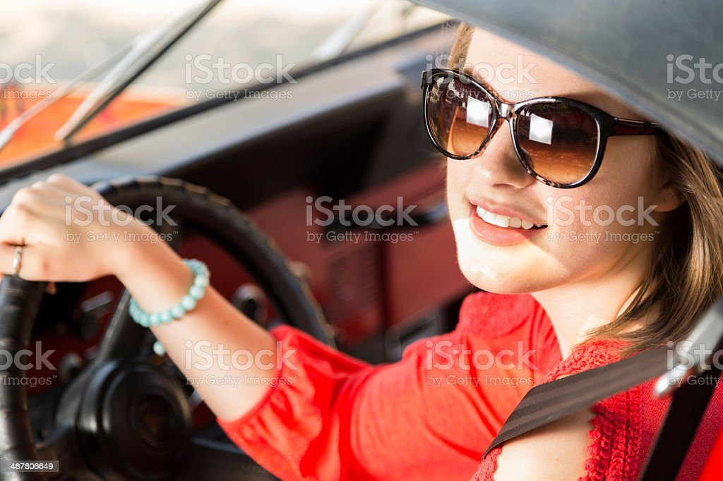 Pretty teenage girl drives convertible vehicle in summer. stock photo