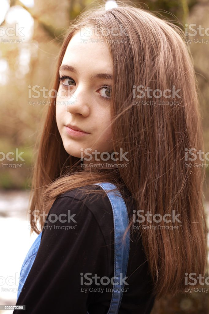 Pretty teenage girl looking over shoulder in an outdoor setting stock photo