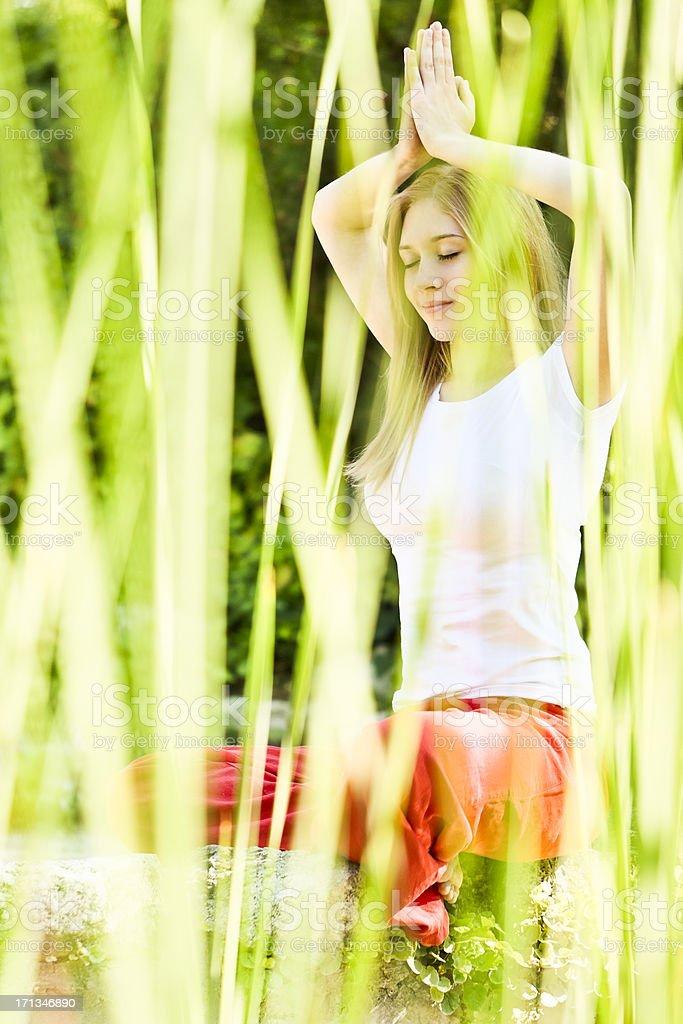 Pretty teenage girl meditating stock photo