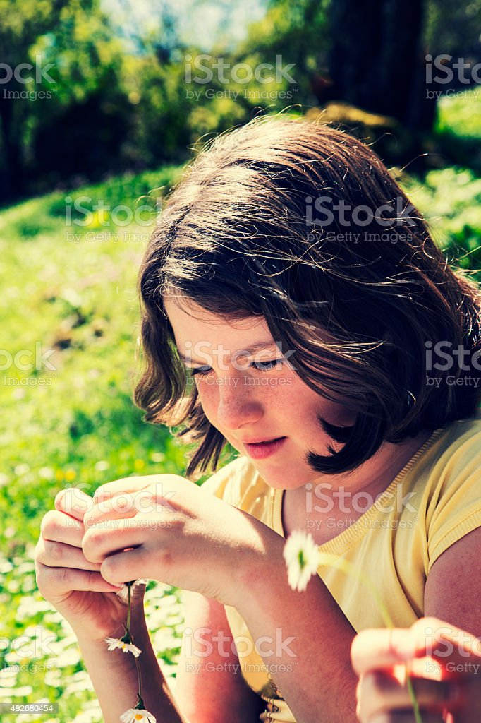 Pretty teenage girl playing with flowers royalty-free stock photo