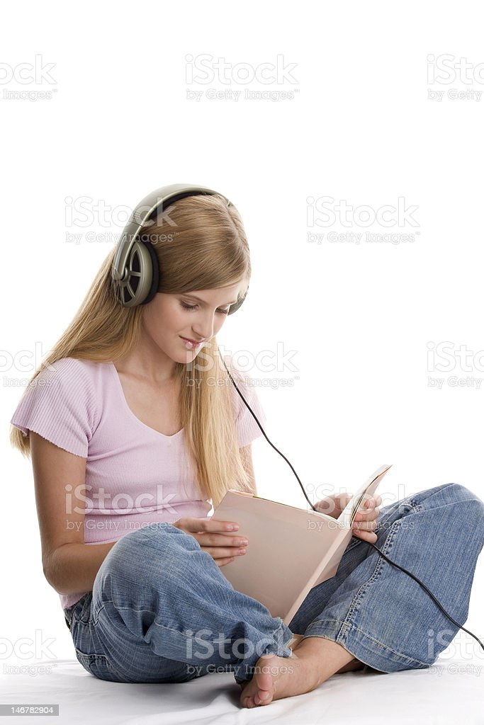 Pretty teenage girl reading book and listening to music royalty-free stock photo