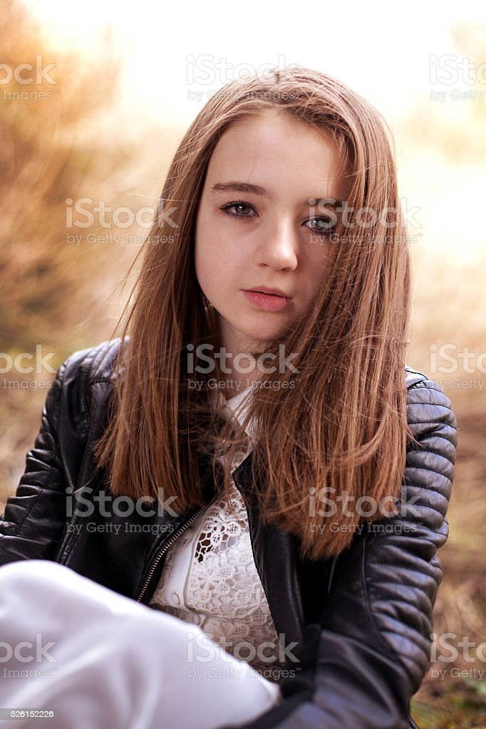 Pretty teenage girl sitting outdoors looking straight to camera stock photo