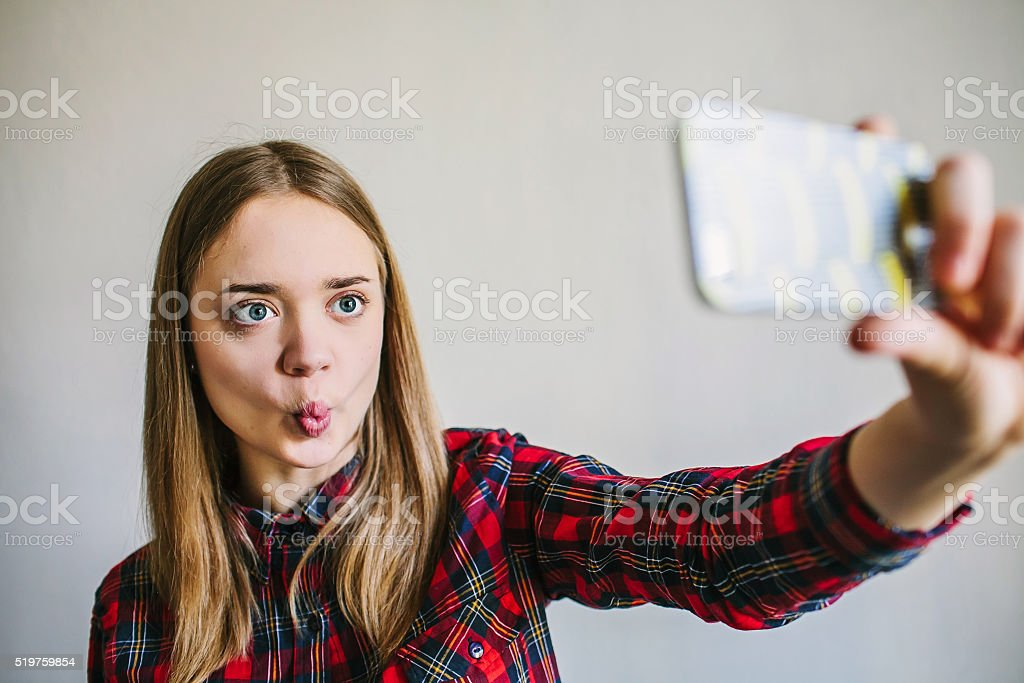 Pretty teenage girl taking selfie and making duck face. stock photo