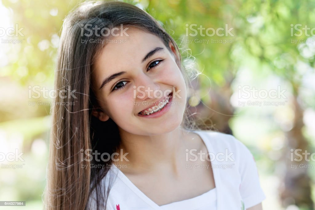 Pretty teenage girl wearing braces smiling cheerfully stock photo