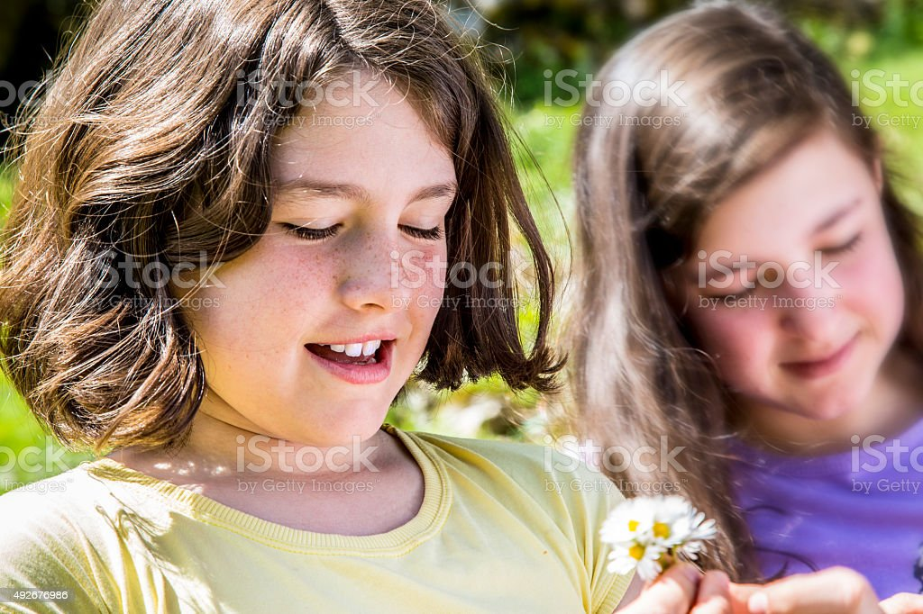 Pretty teenage girls playing with flowers royalty-free stock photo