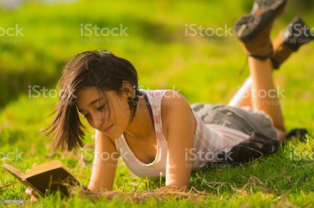 Pretty teenage hispanic girl wearing white top and shorts lying stock photo