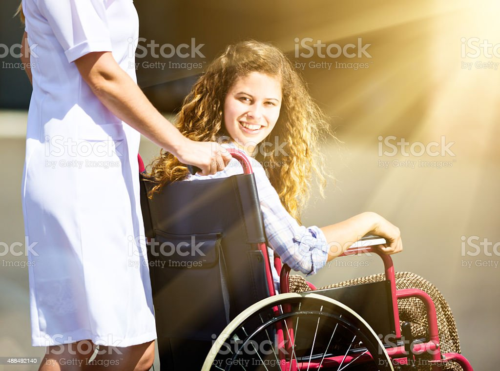 Pretty teenager being pushed in wheelchair looks around, smiling stock photo
