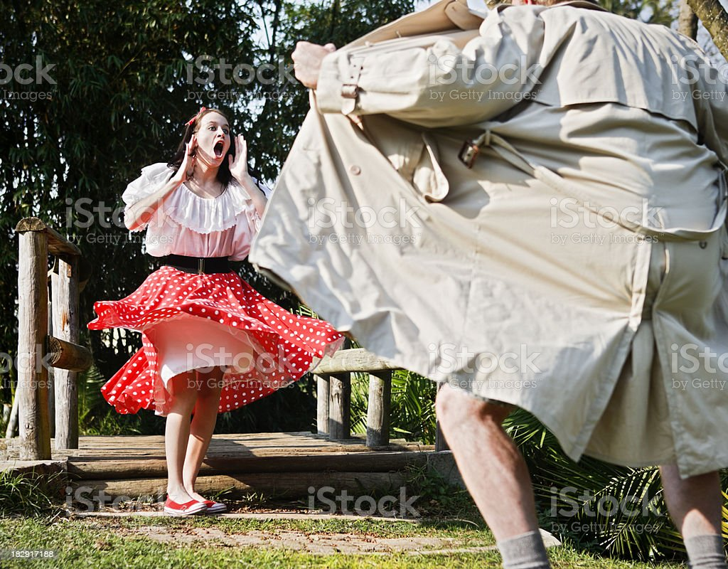 Pretty teenager is horrified by flasher in park stock photo