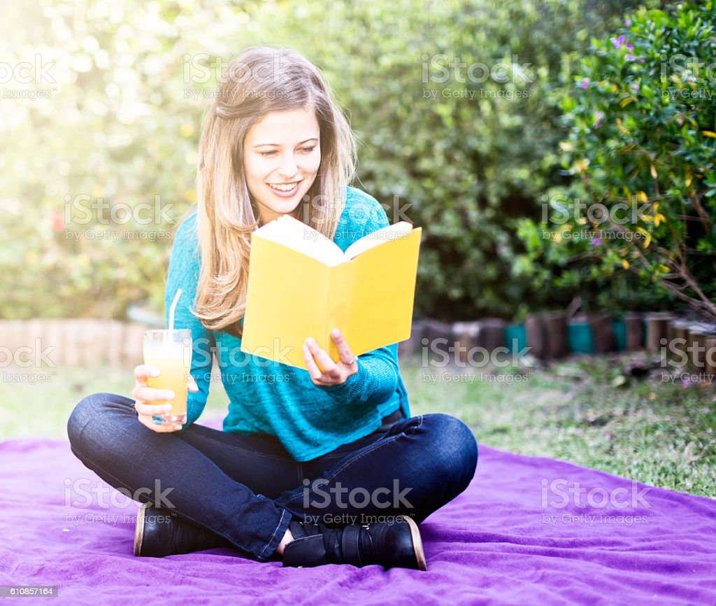 Pretty teenager sitting in garden with book and fruit juice stock photo
