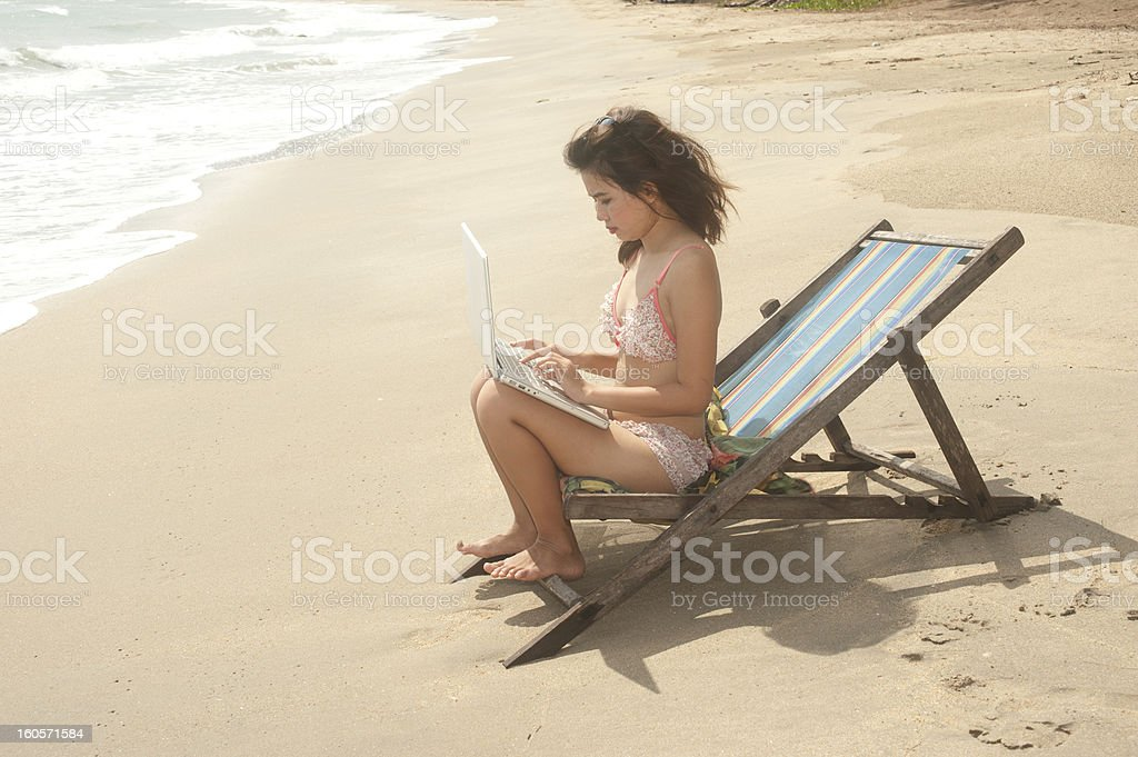 Pretty Thai woman working on the beach. royalty-free stock photo