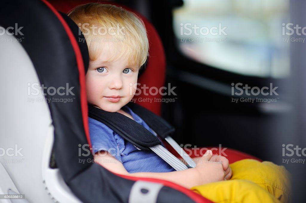 Pretty toddler boy sitting in car seat stock photo