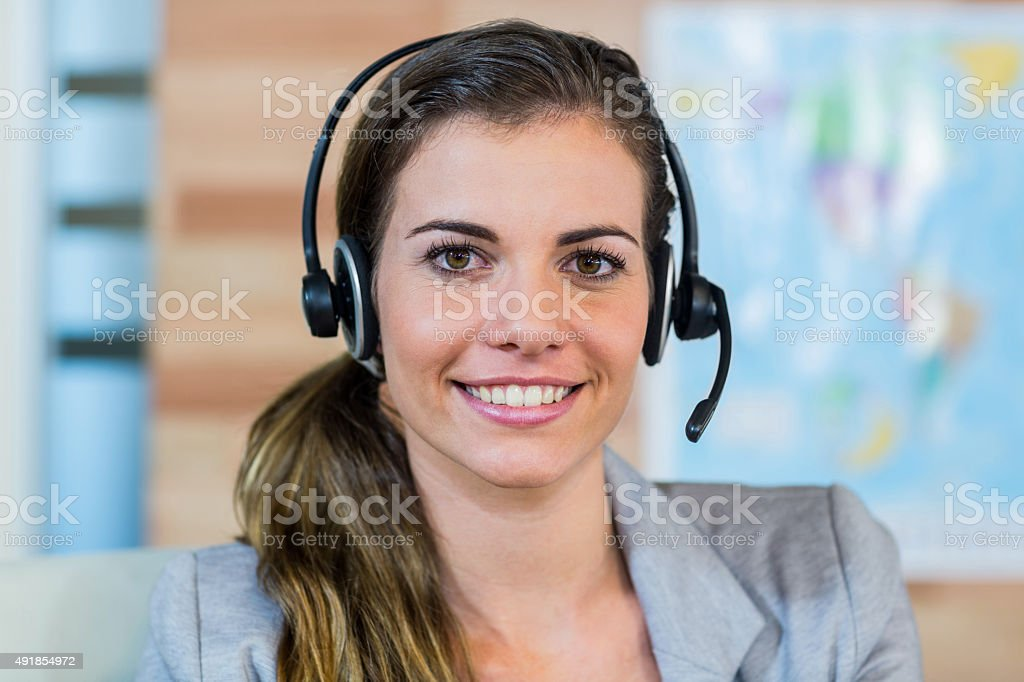 Pretty travel agent smiling at camera stock photo