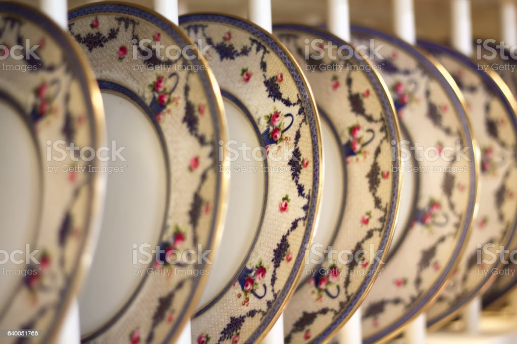 Pretty Vintage Floral Dinner Plates Lined Up in Plate Rack stock photo