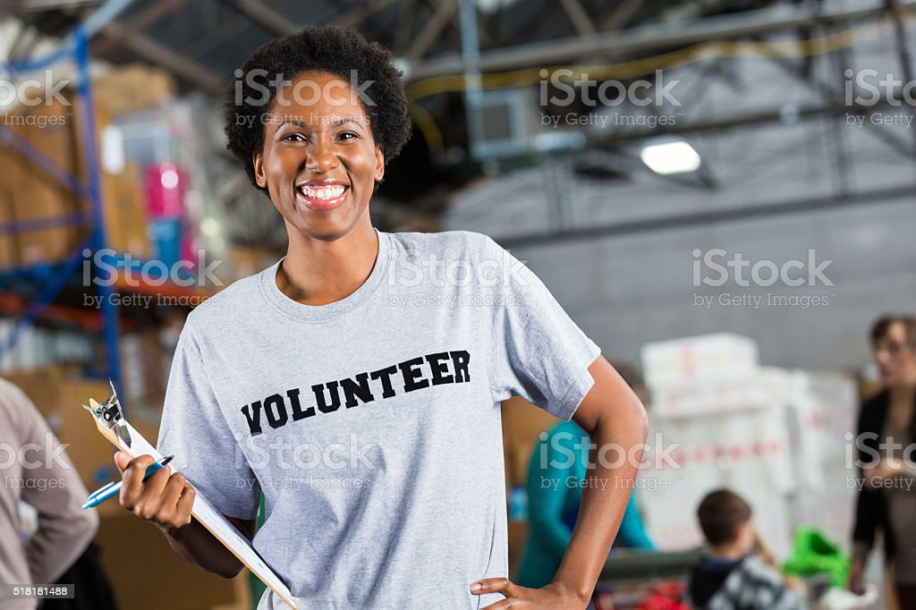 Pretty volunteer at food and clothing drive stock photo