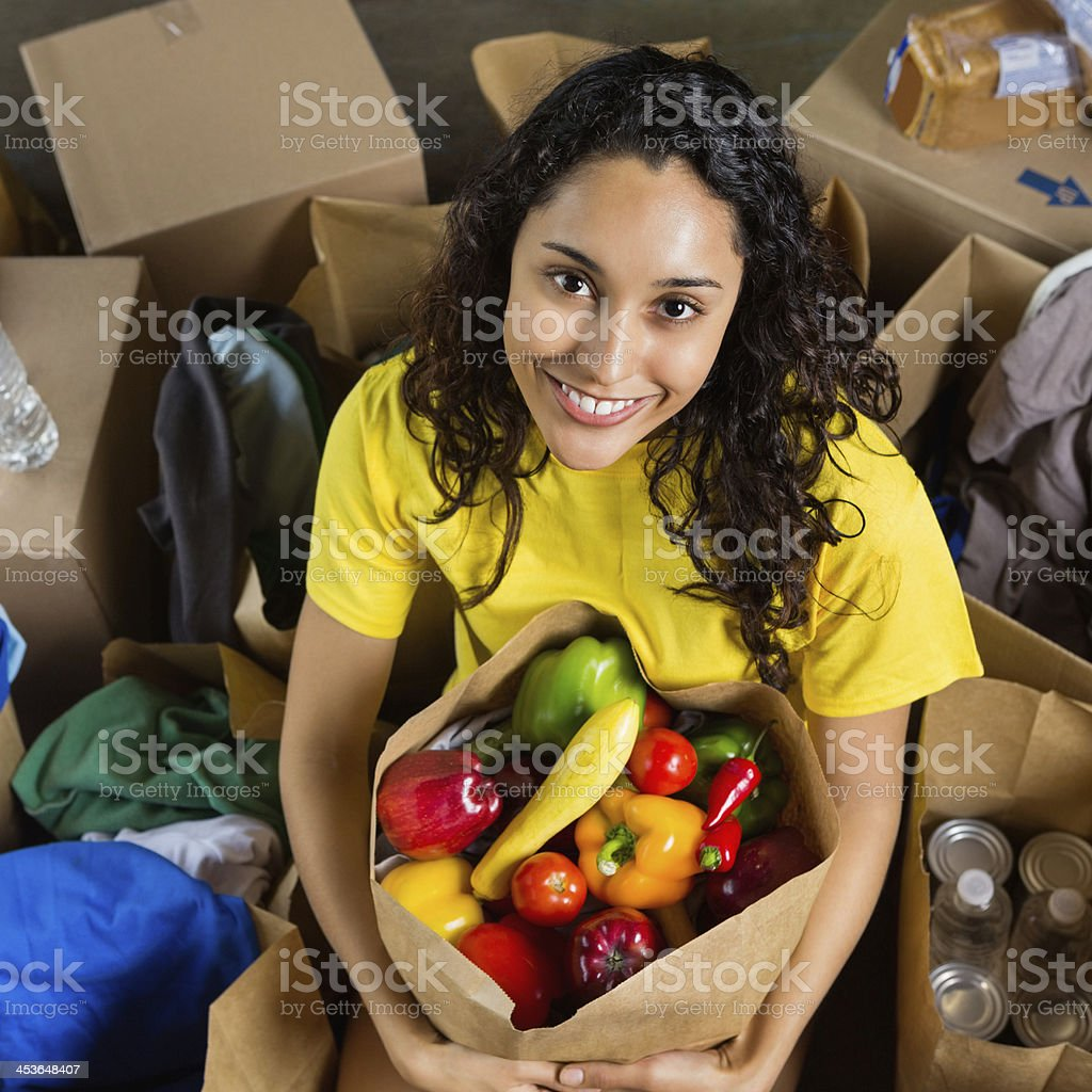 Pretty volunteer with bag of healthy food donations royalty-free stock photo