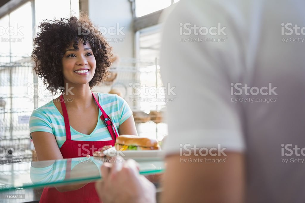 Pretty waitress giving sandwich to customer stock photo