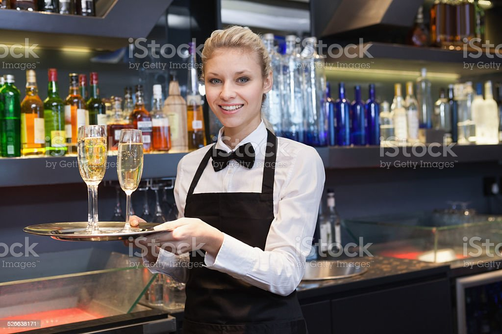 Pretty waitress holding a tray of champagne stock photo