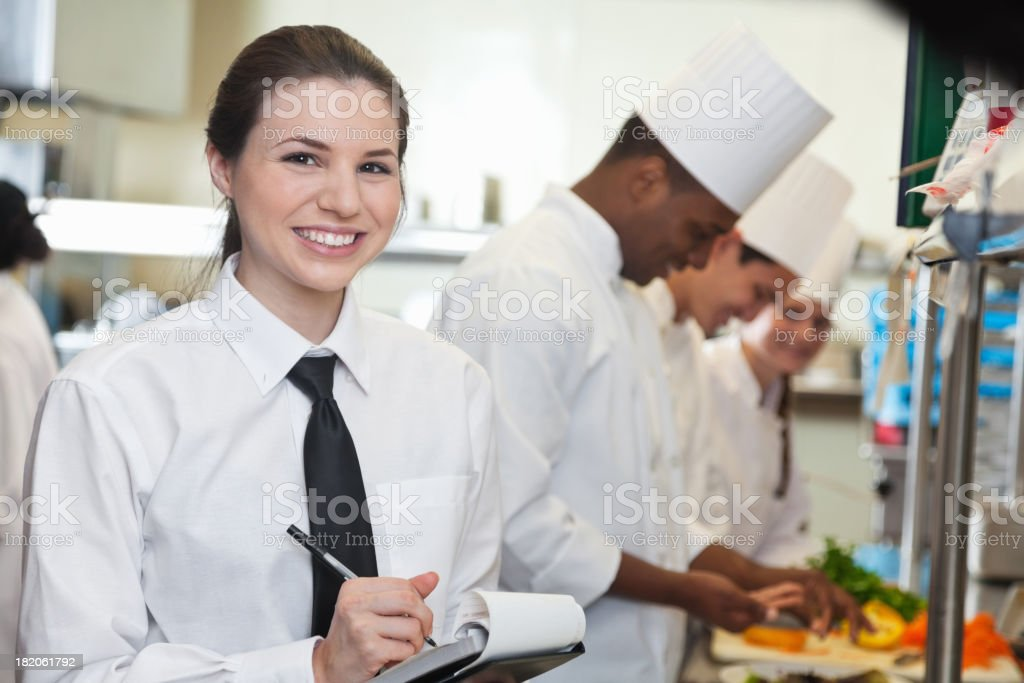 Pretty waitress in restaurant kitchen with chefs preparing food stock photo