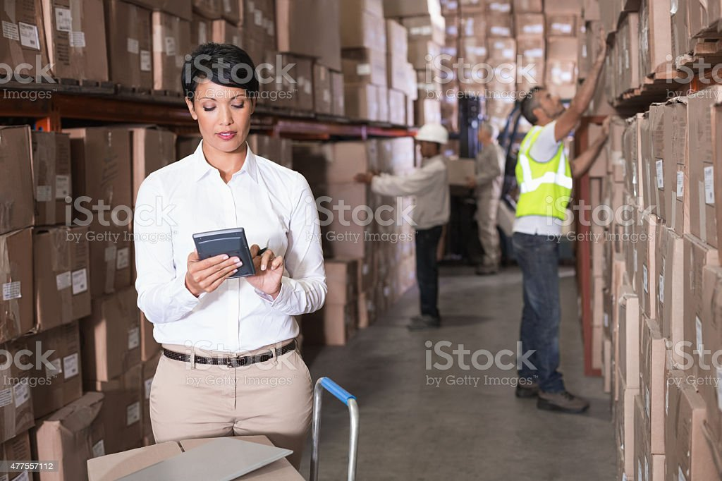 Pretty warehouse manager using calculator stock photo