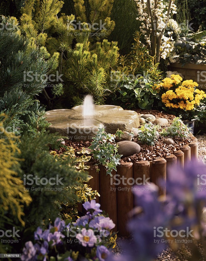 Pretty water fountain in colourful garden flowerbed stock photo