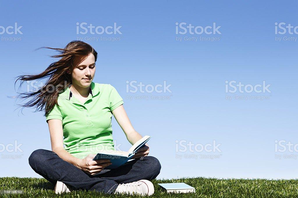 Pretty windblown brunette reads against blue sky royalty-free stock photo