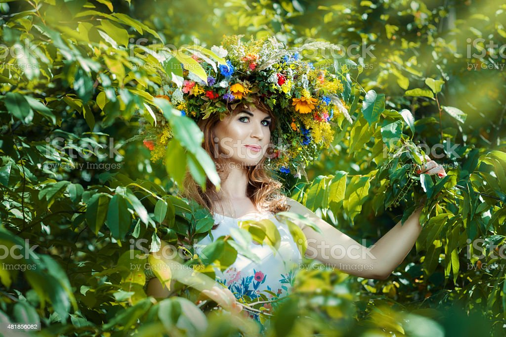 Pretty woman among tree leaves. stock photo