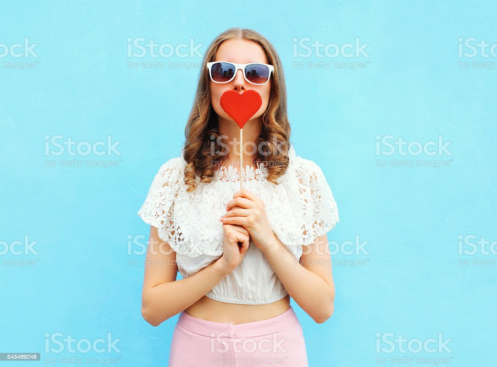 Pretty woman and lollipop over colorful blue background stock photo