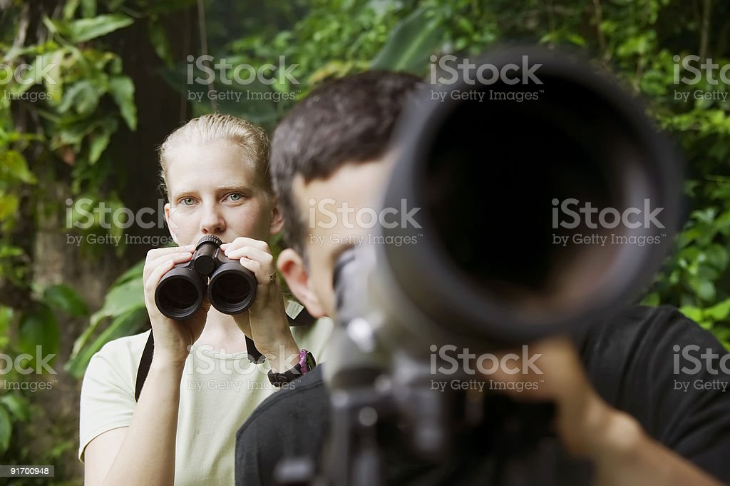 Pretty Woman and Man with Scopes in Jungle royalty-free stock photo