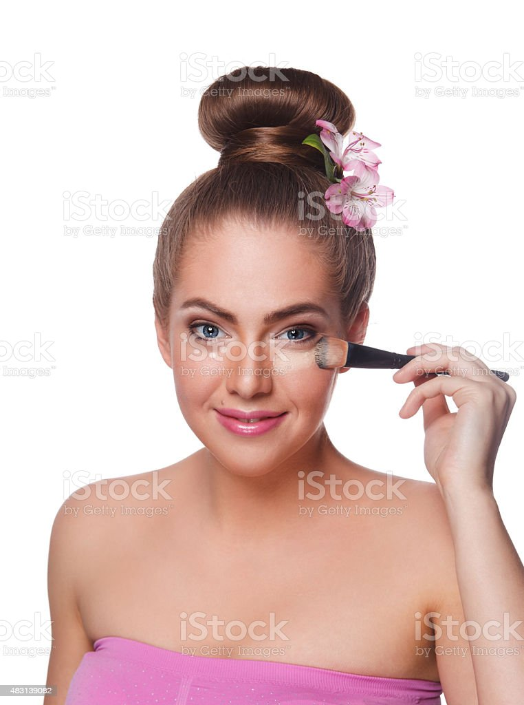 Pretty woman applying concealer with brush stock photo