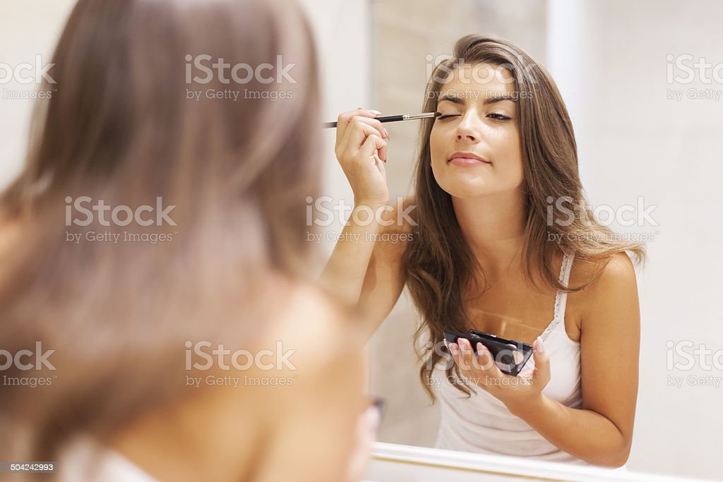 Pretty woman applying eyeshadow in front of a mirror stock photo
