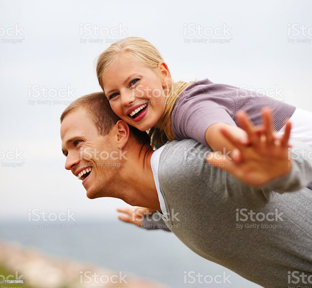 Pretty woman being carried on a man's back, hands outstretched stock photo