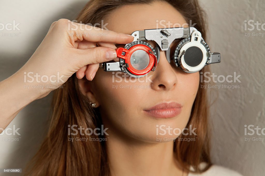pretty woman checks vision in an ophthalmologist with corrective lenses stock photo
