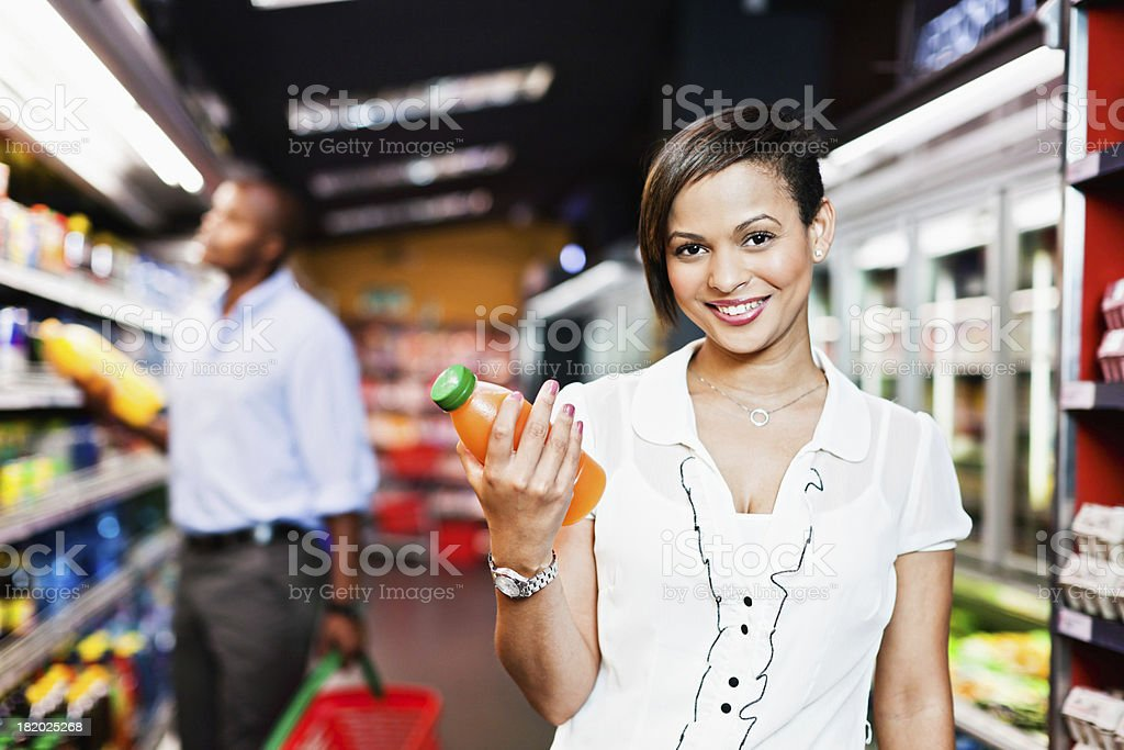 Pretty woman chooses orange juice in supermarket and smiles royalty-free stock photo