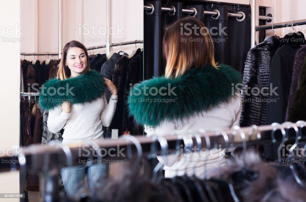 Pretty woman customer examining new fur neckpiece stock photo