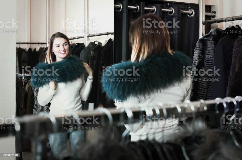 Pretty woman customer examining new fur neckpiece stock photo