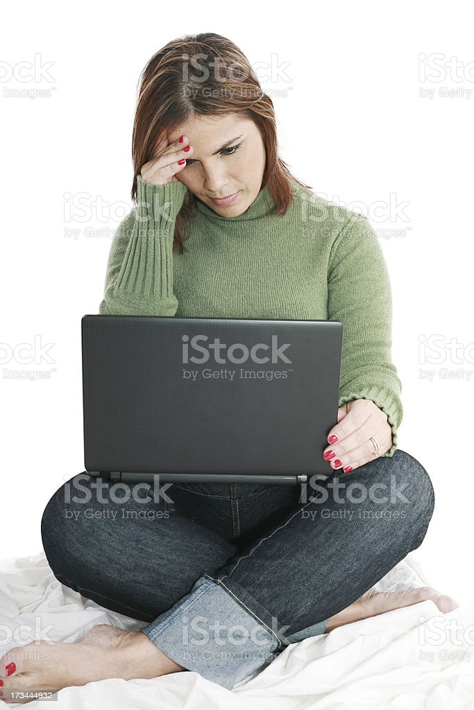 Pretty woman deep in thought while looking at laptop royalty-free stock photo