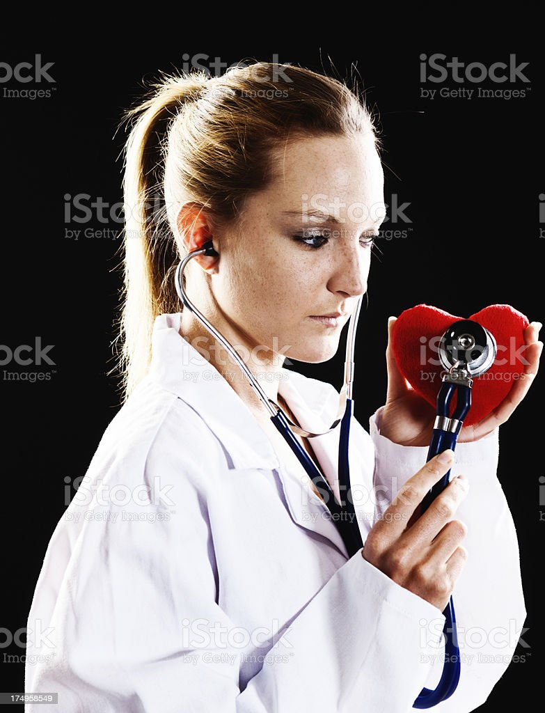 Pretty woman doctor checks Valentine heart with stethoscope royalty-free stock photo
