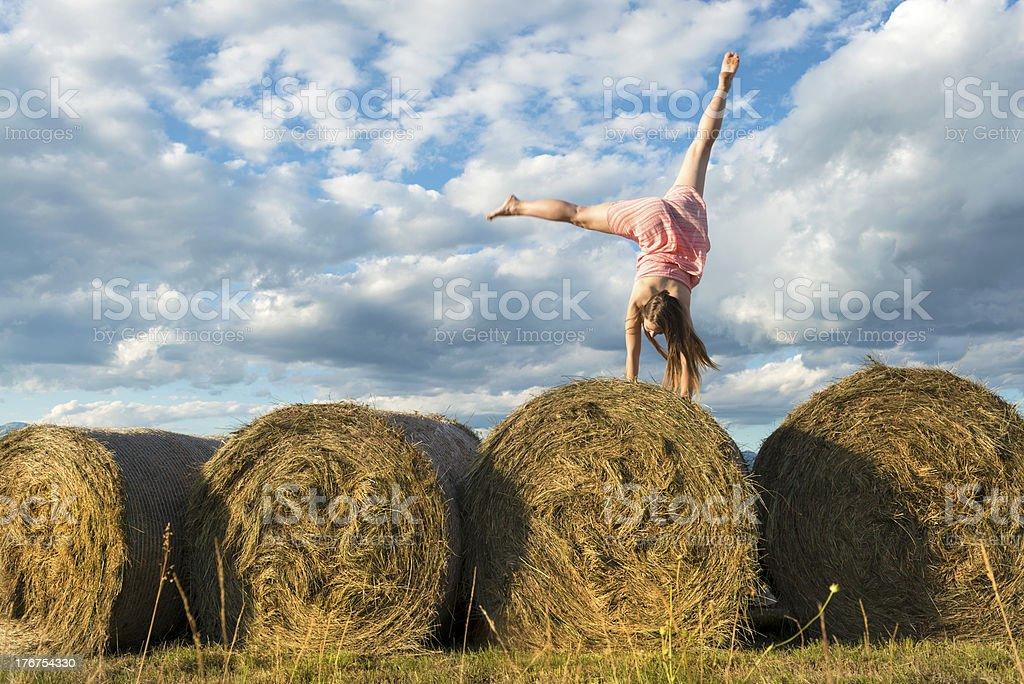 Pretty Woman Doing Cartwheel on Bales of Grass royalty-free stock photo