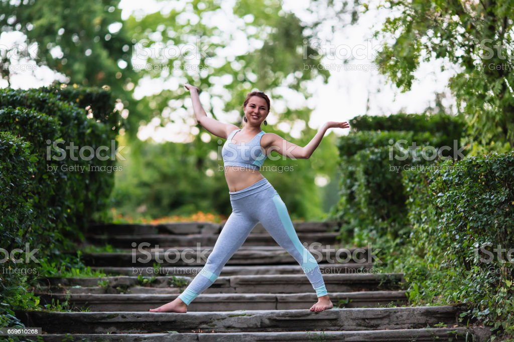 Pretty woman doing yoga exercises in the park stock photo