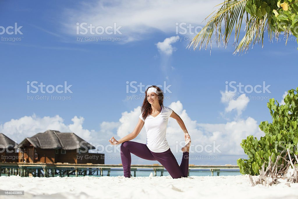 Pretty woman doing yoga exercises on the tropical  beach royalty-free stock photo