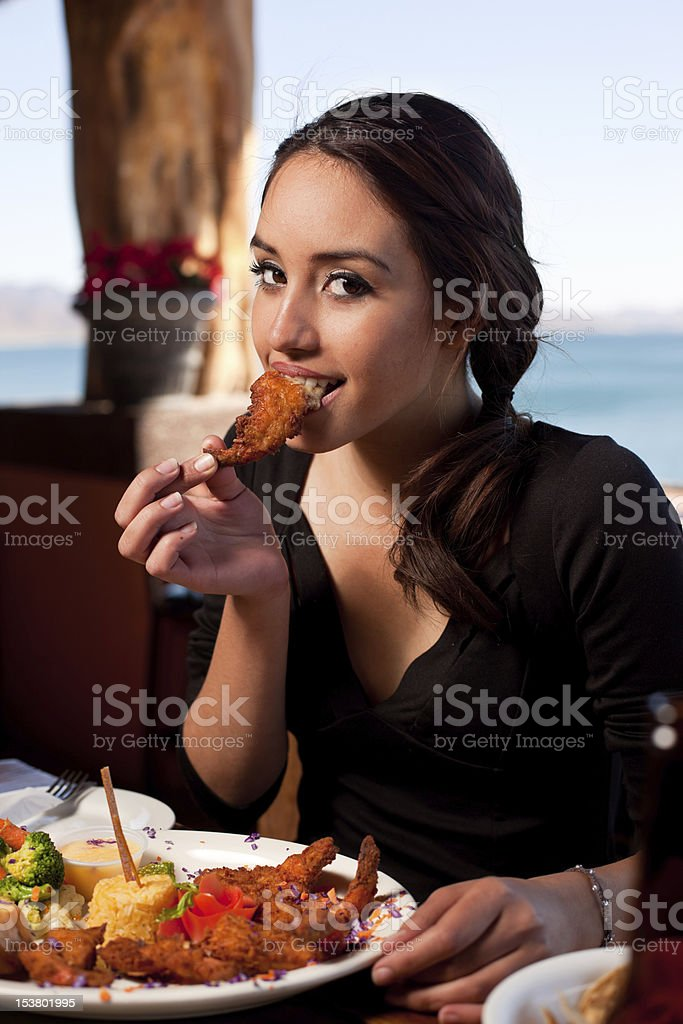 Pretty Woman Eating Fried Shrimp stock photo