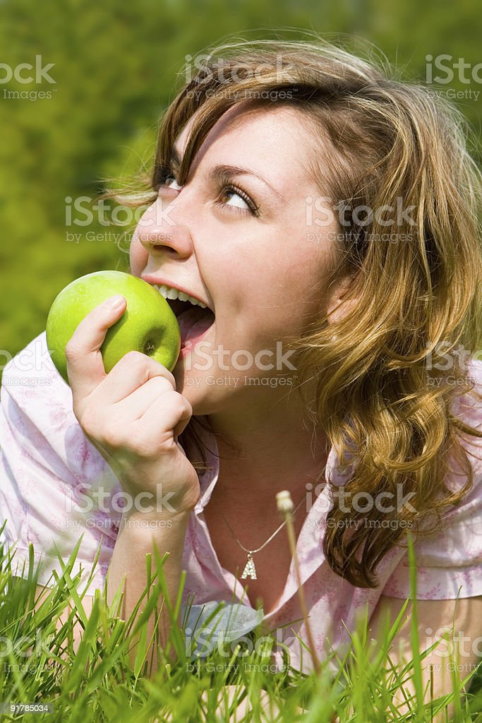 pretty woman eating green apple on the summer glade royalty-free stock photo