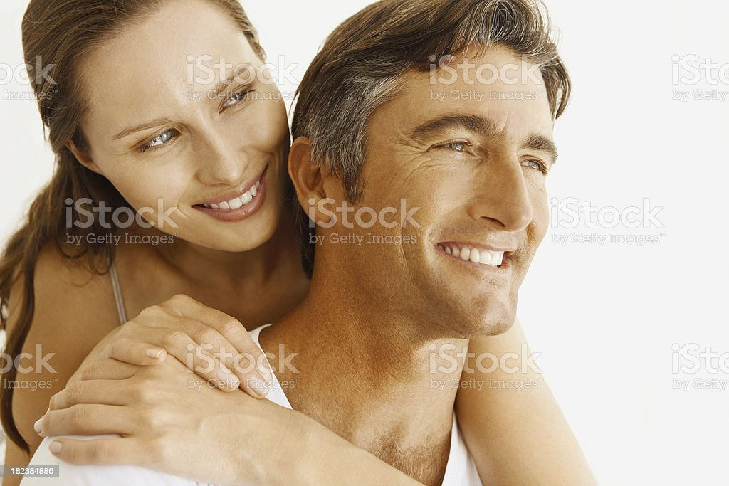 Pretty woman embracing a mature man from behind royalty-free stock photo