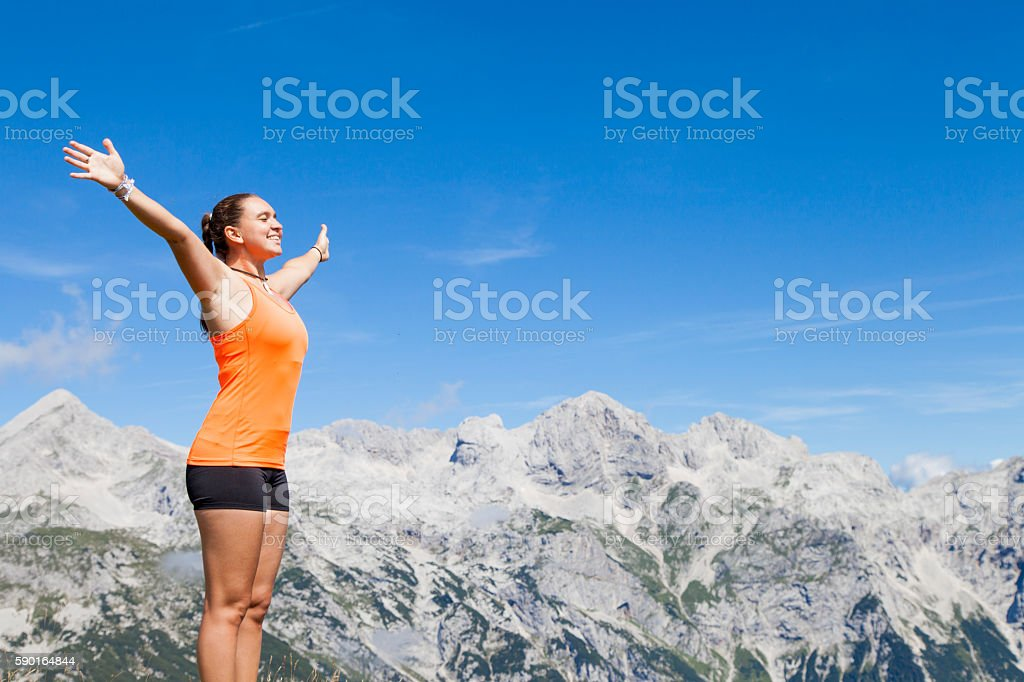Pretty woman hiker standing with raised hands stock photo