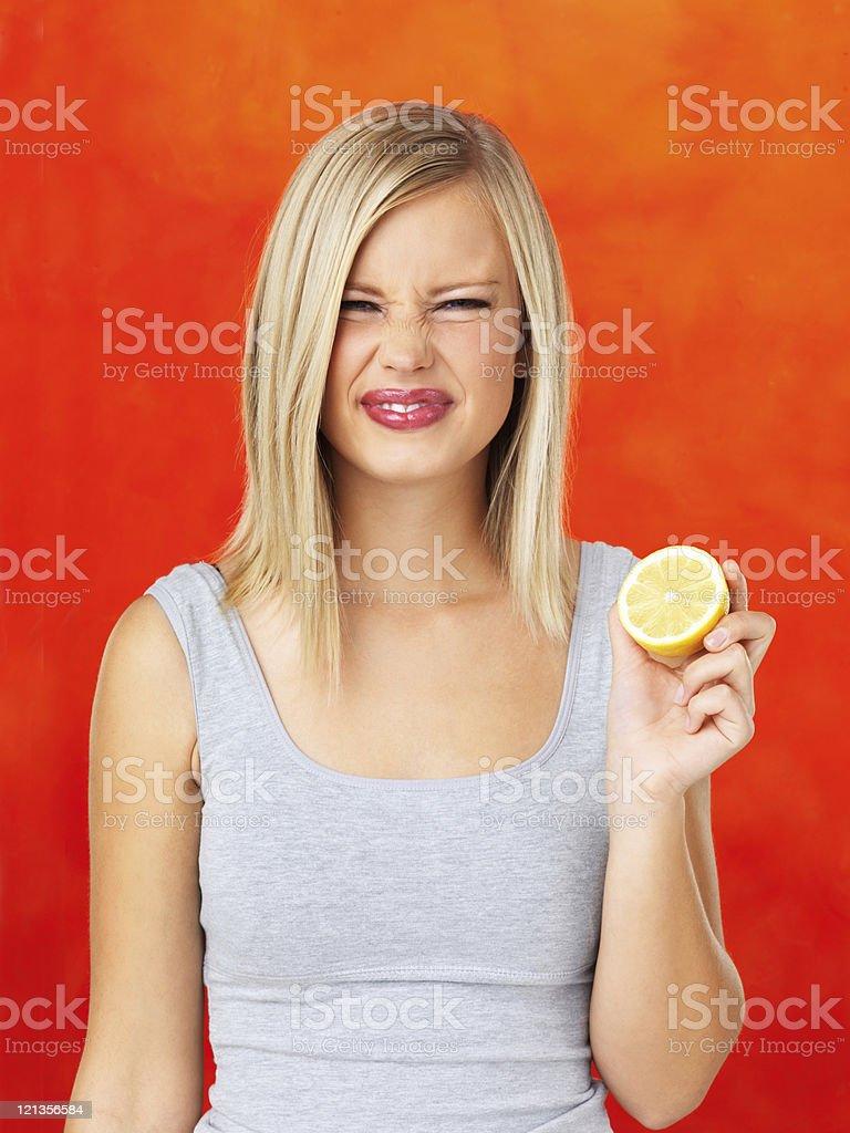 Pretty woman holding a sour lemon stock photo
